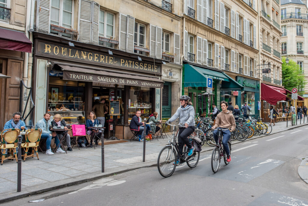 People Riding Bicycles In Marais In Paris