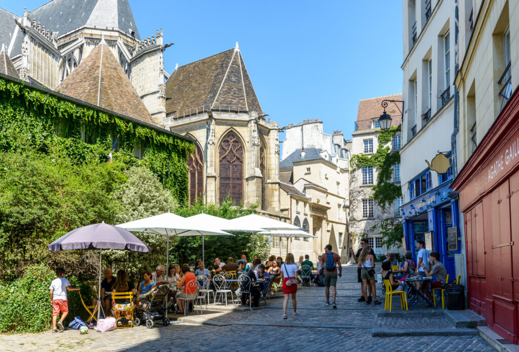 A Small Pedestrian Cobbled Street In The Old District Of Le Marais In Paris, France, Behind Saint Gervais Church, With People Having Lunch On The Shady Terrace Of A Restaurant By A Sunny Summer Day.